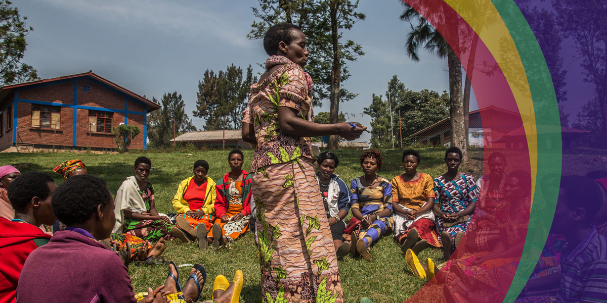 African Woman Speaks to Women Seated Around Her